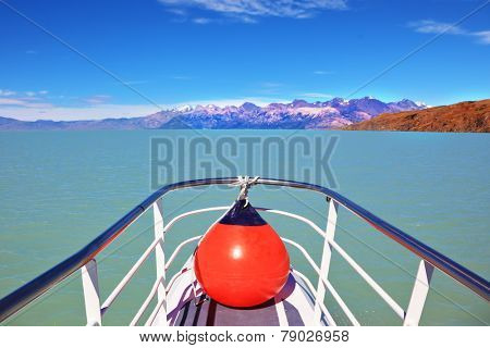 Excursion on the tourist boat on Lake Viedma.  White-blue huge icebergs float near a ship board. Ice and sun Patagonia