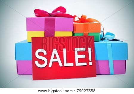 a pile of gift boxes of different colors and a red signboard with the word sale written in it