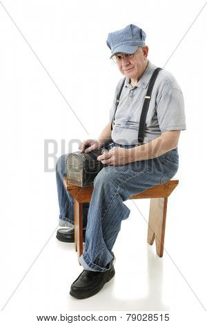 A senior adult train engineer sitting on an old wooden bench with his lunch box and pocket watch.  On a white background.