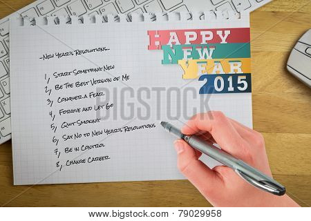 Businesswomans hand writing with pen against overhead of graph paper on keyboard