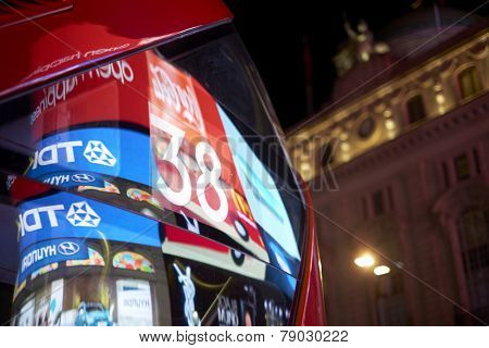 LONDON, UK - DECEMBER 19: Detail of London red bus line 38 reflecting lights of Piccadilly Circus at night. December 19, 2014 in London.