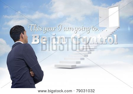 Unsmiling asian businessman with arms crossed against steps leading to open door in the sky