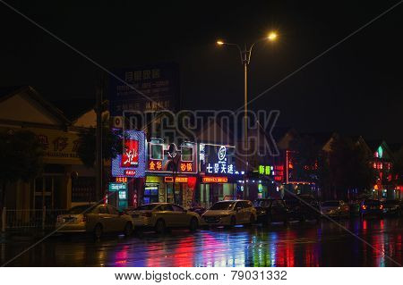 Colorful Chinese Neon Advertising With Reflections On Wet Road