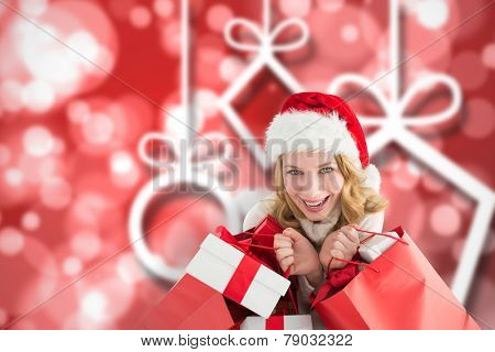 Girl in winter fashion holding presents and shopping bags against blurred christmas background