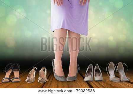 Mid section of woman in dress with heels against shimmering light design over boards