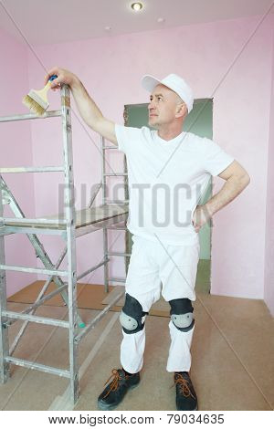 Plasterer in white clothes and kneepads standing near scaffolding and looking at his work in pink room