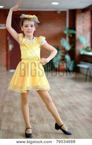 Beautiful dancer in yellow satin dress stands raising her hand up in hall with brick walls