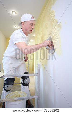 Plasterer applied with a trowel yellow decorative plaster on the wall