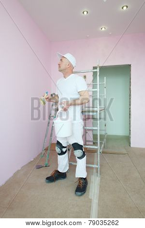 Plasterer in white clothes and kneepads looking at his work in pink room