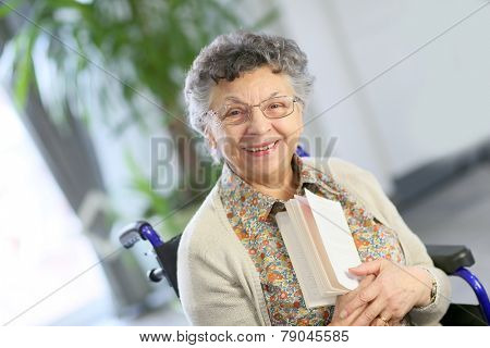 Elderly woman in wheelchair reading book