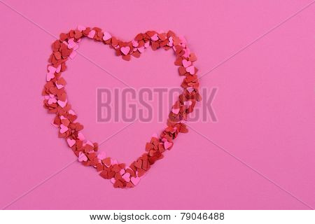 High angle closeup of a bunch of pink and red paper hearts arranged into a larger heart shape. Horizontal format on a pink paper background with copy space.