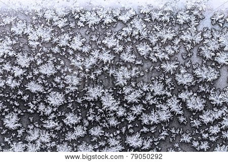 Snowflakes And Frost On Frozen Window Pane