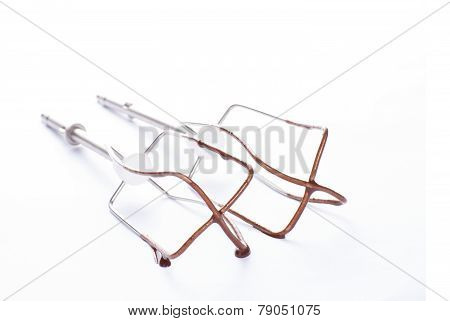 Egg beaters or whisk after use with chocolate cream on white background