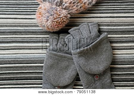 Woolen Hat And Gloves On A Striped Knitting Background