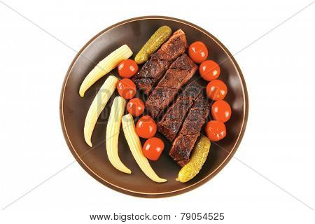 fresh red beef meat served with baby corns and cherry tomatoes on dark plate isolated on white background