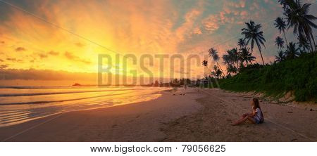 Young lady relaxing on the sandy beach and enjoying bright sunset