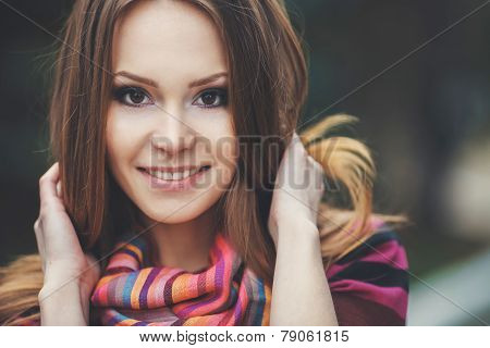 Portrait of a young brunette with autumn scarf.