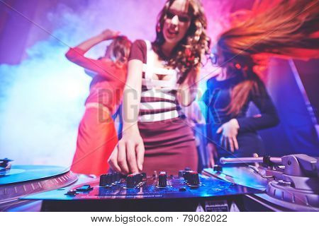 Girl adjusting deejay equipment with dancing friends behind