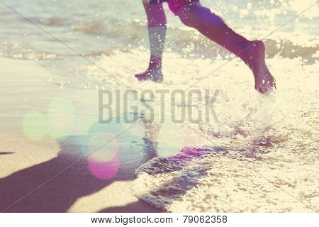Child running at the beach, runner has motion blur. Focus on san