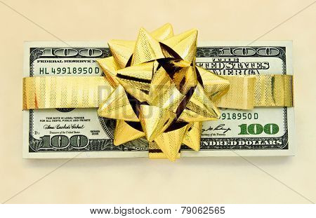 100 dollar bills wraped up with a gold ribbon