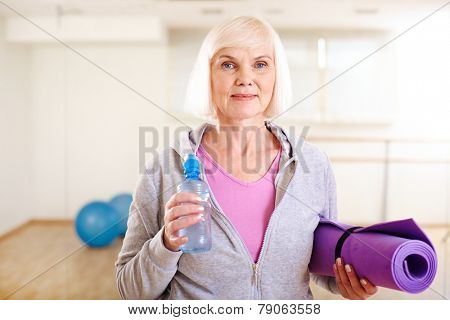 Portrait of aged woman with bottle of water and rug looking at camera