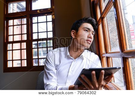 handsome young businessman drinking coffee in cafe and using tablet computer