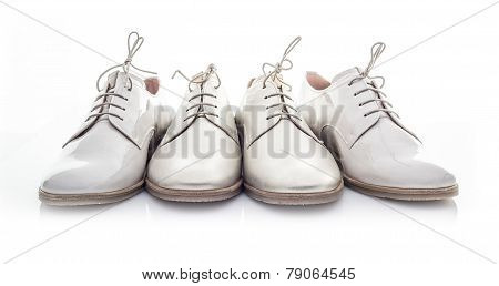Four White Shoes On A White Background