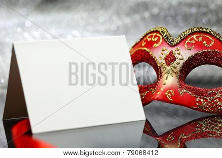 Vintage carnival mask and white blank card in front of glittering background