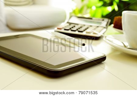 detail of a desk with a tablet, a calculator and a cup of coffee or tea in an office with a nice atmosphere