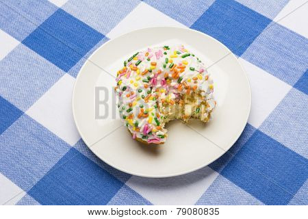 A freshly bitten, delicious icing coated cake donut with sweet sprinkles on a classic, checkered diner tablecloth