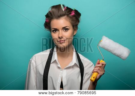 Portrait of funny cute brunette woman in hair curlers wearing wh