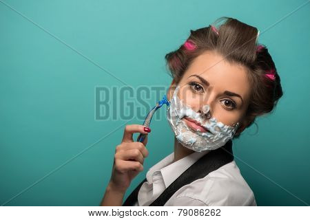 Cute brunette woman in hair curlers posing with foam on face sh