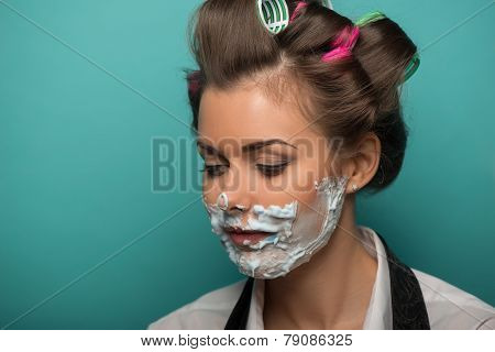 Cute brunette woman in hair curlers playing fool with foam