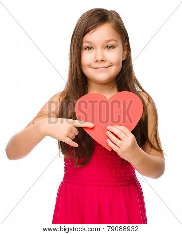 Portrait of a little girl holding red heart and pointing to it using index finger, isolated over white