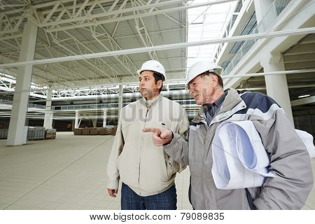 Architect and engineer worker with blueprints in a building under construction