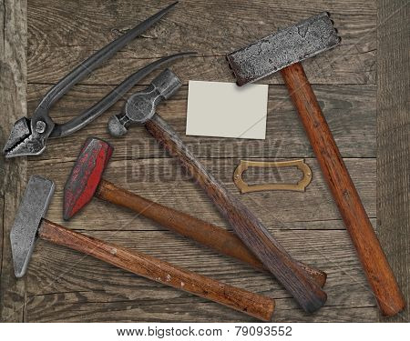 vintage blacksmith or metalwork tools over wooden bench, blank plate and business card for your text