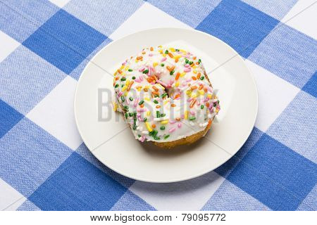 A fresh, delicious icing coated cake donut with sweet sprinkles on a classic, checkered diner tablecloth D