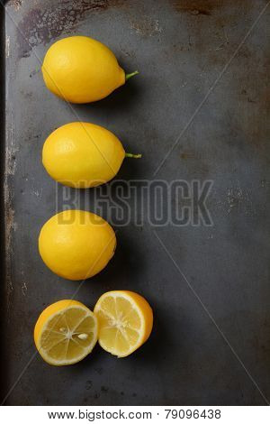High angle shot of a group of lemons, three whole and one cut, on a metal baking sheet. Vertical format.
