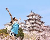 stock photo of sakura  - Happy woman traveler enjoy view with sakura cherry blossoms tree and castle on vacation while spring in japan asian - JPG