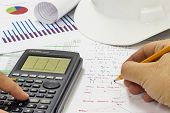 foto of structural engineering  - Civil Design Engineer is making structural analysis calculations using a scientific calculator - JPG
