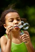 stock photo of summer fun  - Portrait of cute girl blowing soap bubbles outdoors  - JPG