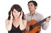 image of serenade  - beautiful girl gesturing silence while young man serenades her with guitar isolated on white - JPG