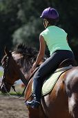 pic of horse riding  - Young girl practices riding her horse in outdoor arena - JPG