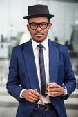 stock photo of cigar  - Attractive black man with a cigar and a glass of cognac - JPG