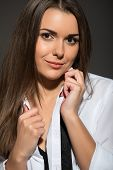 stock photo of strip-tease  - Sexy young Caucasian brunette woman wearing men white shirt - JPG