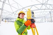 stock photo of theodolite  - female surveyor worker working with theodolite transit equipment at road construction site outdoors - JPG