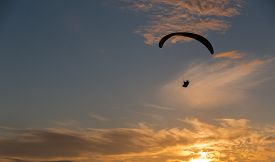 pic of glider  - A para glider sails over the Pacific Ocean into a beautiful sunset - JPG