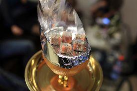 image of shisha  - Coals on the orange bowl of shisha in the arabic cafe - JPG