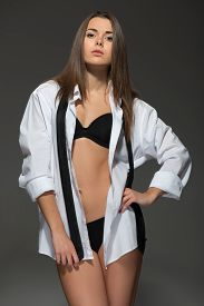 stock photo of strip tease  - Sexy young Caucasian brunette woman wearing men white shirt - JPG