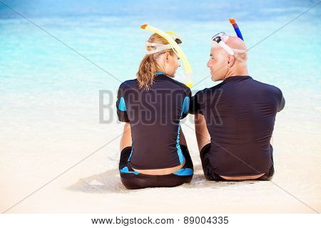 Back side of happy diver couple sitting on the beach and looking on each other with love, wearing diving equipment and preparing to snorkeling, enjoying extreme sport and active summer vacation